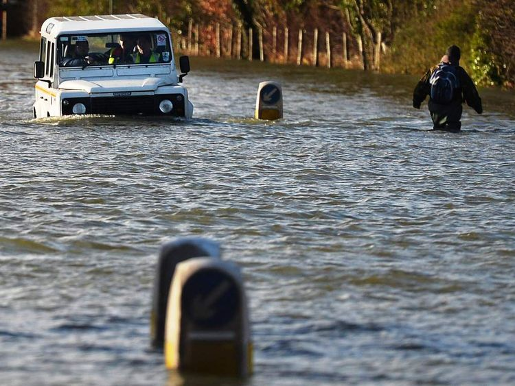 A vehicle drives along a flooded road as a man (R) wades in Runnymede, south-west of London