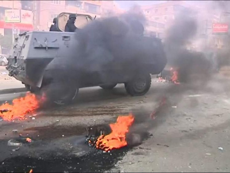 Riot vehicle and flames in Cairo
