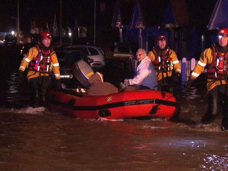 Couple evacuated in boat from flooded street