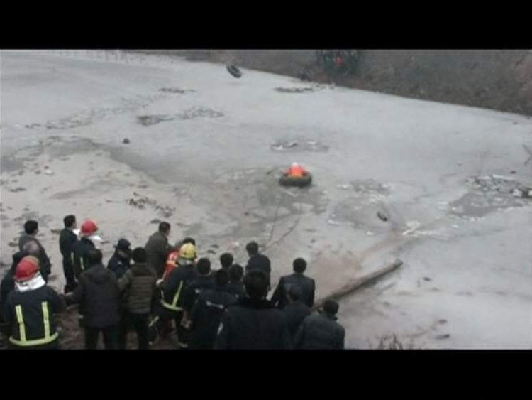 Rescue workers use tires to wade into a river to search for the bodies of six children