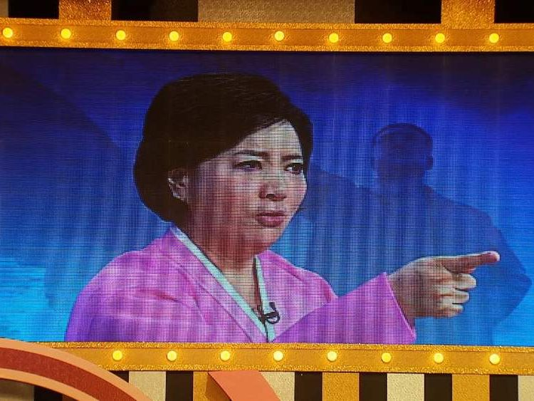 A woman impersonates the stern delivery of a North Korean newsreader.