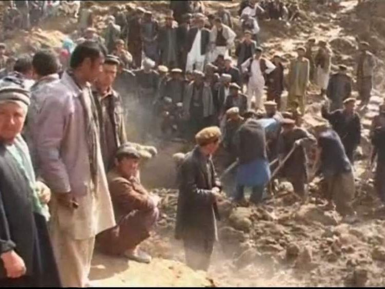 Villagers dig and sift through the mud after a landslide hit the village of Hobo Barik in Afghanistan.