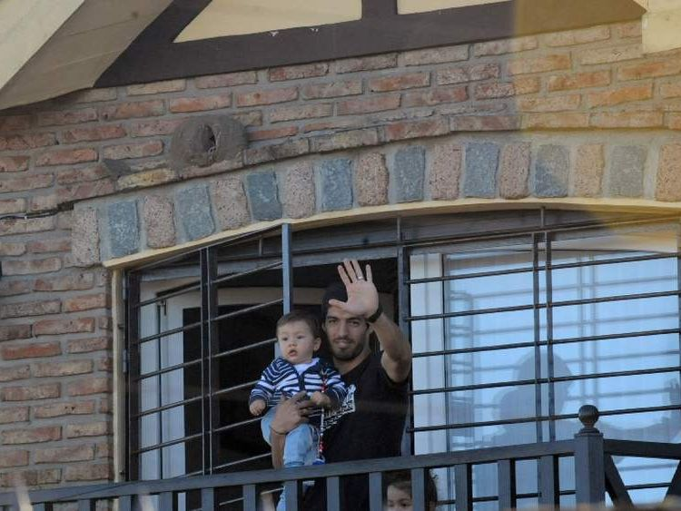 Uruguay striker Luis Suarez back home with one of his children