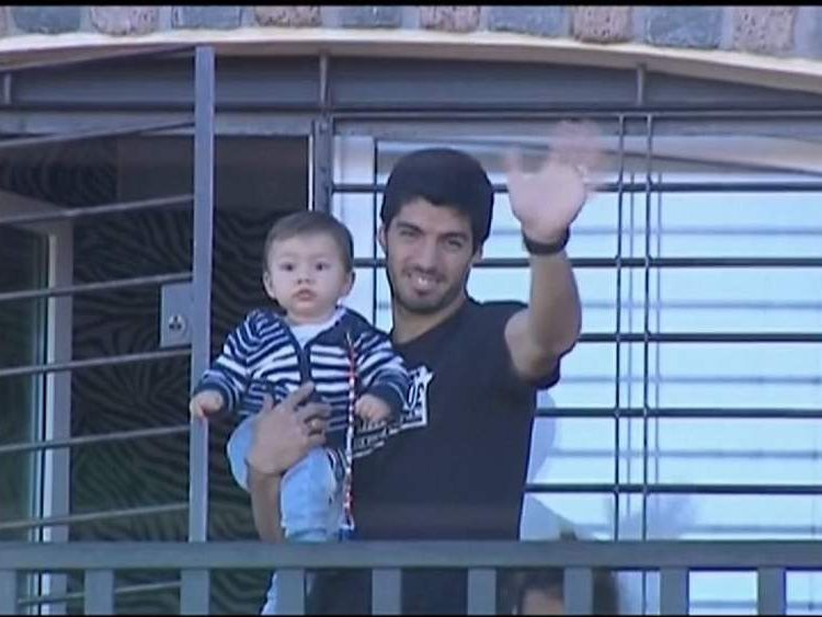 Luis Suarez with son waves to fans gathered outside his house in Montevideo