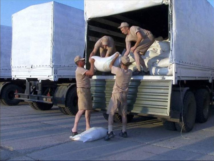 Russian men load sacks on to a truck bound for eastern Ukraine