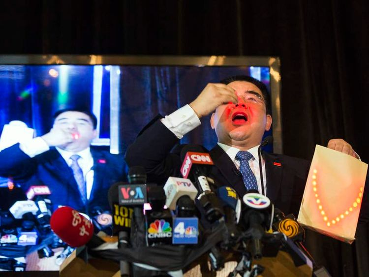 Chinese billionaire Chen Guangbiao performs magic tricks during a lunch he sponsored for hundreds of needy New Yorkers at Loeb Boathouse in New York's Central Park