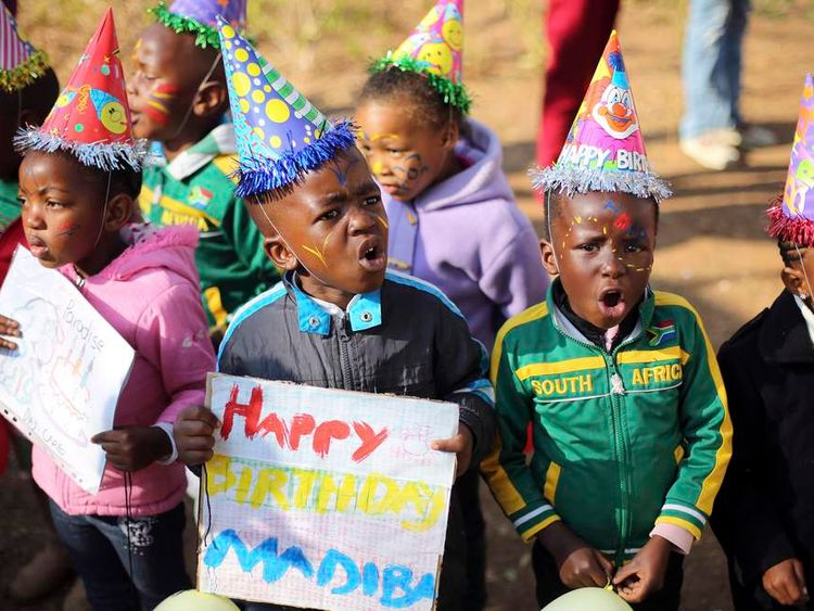 Children hold placards as they gather to wish former President Nelson Mandela happy birthday outside the Medi-Clinic Heart Hospital, where he is being treated, in Pretoria