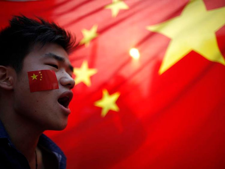 A demonstrator shouts slogan during a protest in front of a Chinese national flag on the 81st anniversary of Japan's invasion of China