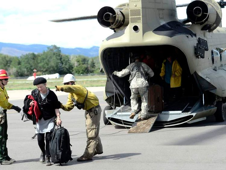 Deborah Haynes is directed off the tarmac at Boulder Municipal Airport after being flown down from Jamestown on a National Guard helicopter in Boulder