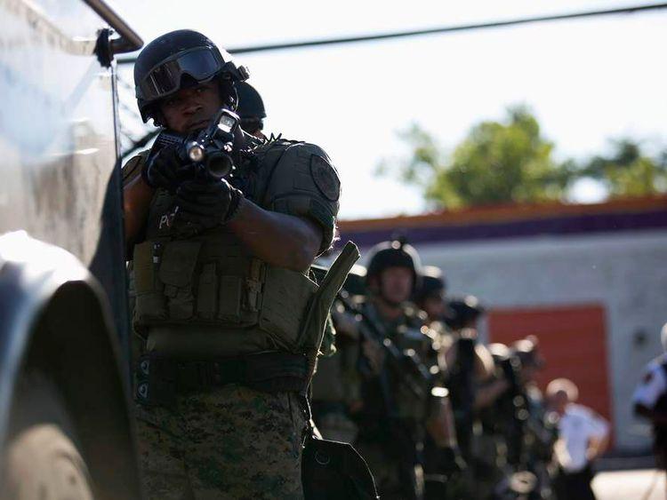 A police officer holds his riot gun in Ferguson, Missouri