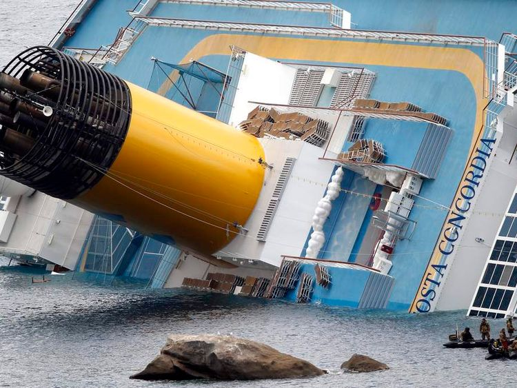 Rescuers on power rafts are seen next to the Costa Concordia cruise ship that ran aground off the west coast of Italy
