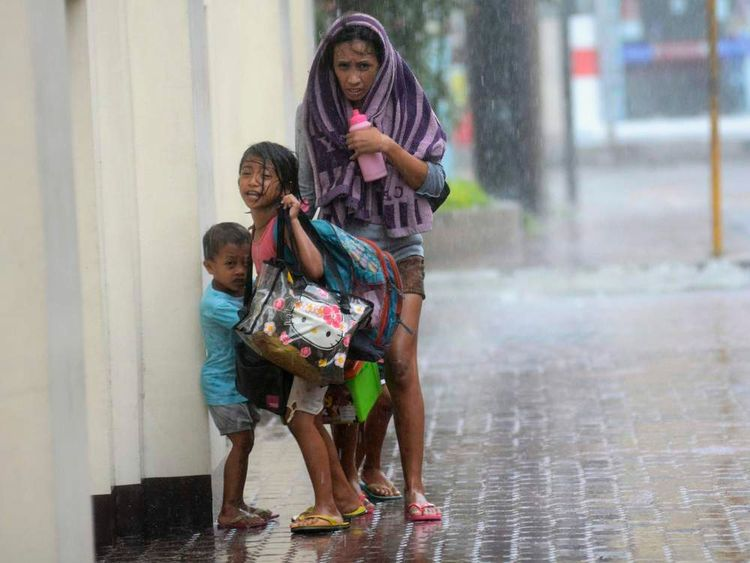 A mother takes refuge with her children as Typhoon Haiyan hits Cebu city