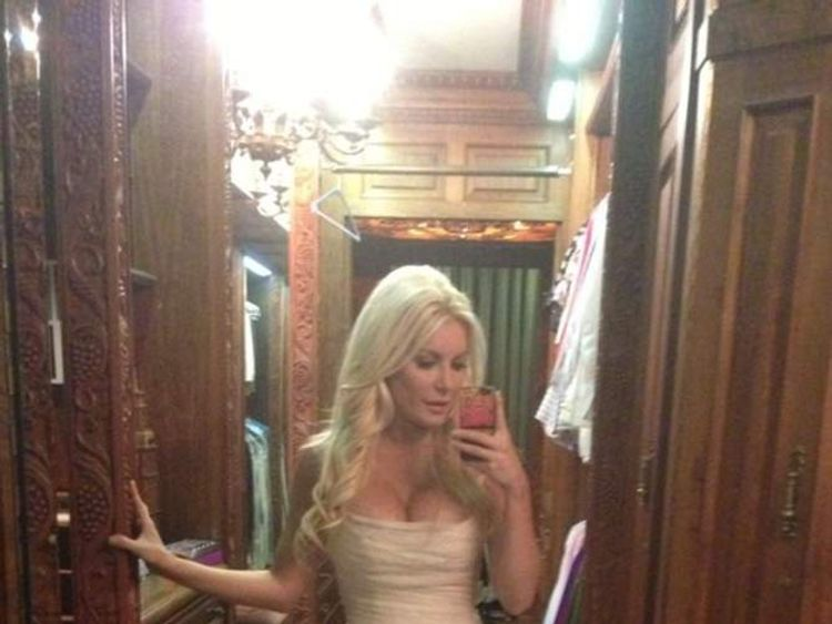 Crystal Hefner takes a photo of her mermaid dress reflected in the mirror