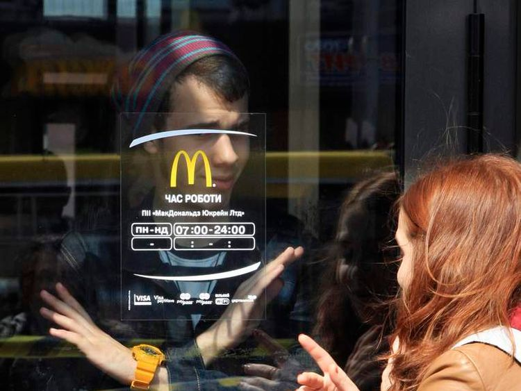 A man gestures to a woman signaling that a McDonald's restaurant is closed for clients in the Crimean city of Simferopol
