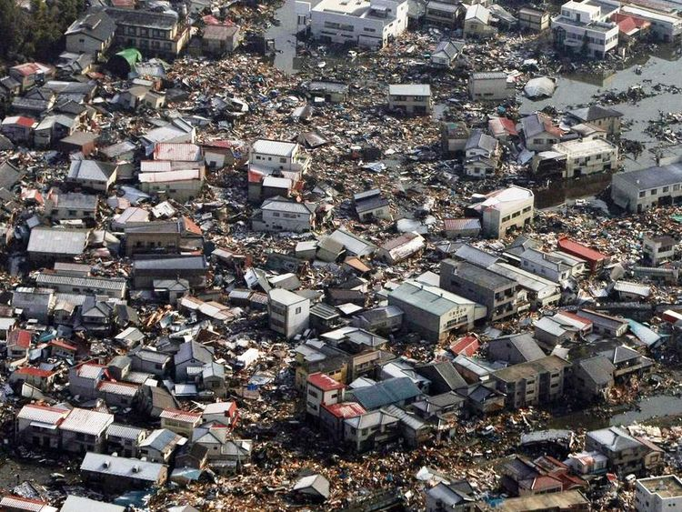 Collapsed houses and debris remain on a field in Kesennuma city, Miyagi prefecture on March 12, 2011