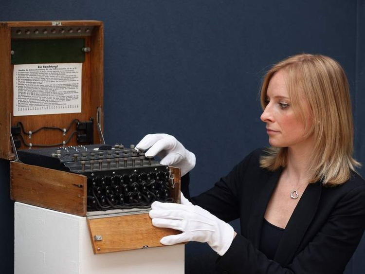 An employee at Christie's auction house examines an Enigma cipher machine