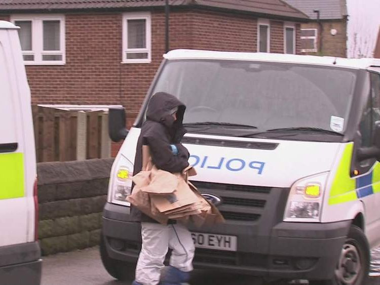 Police officer carries bags to a van