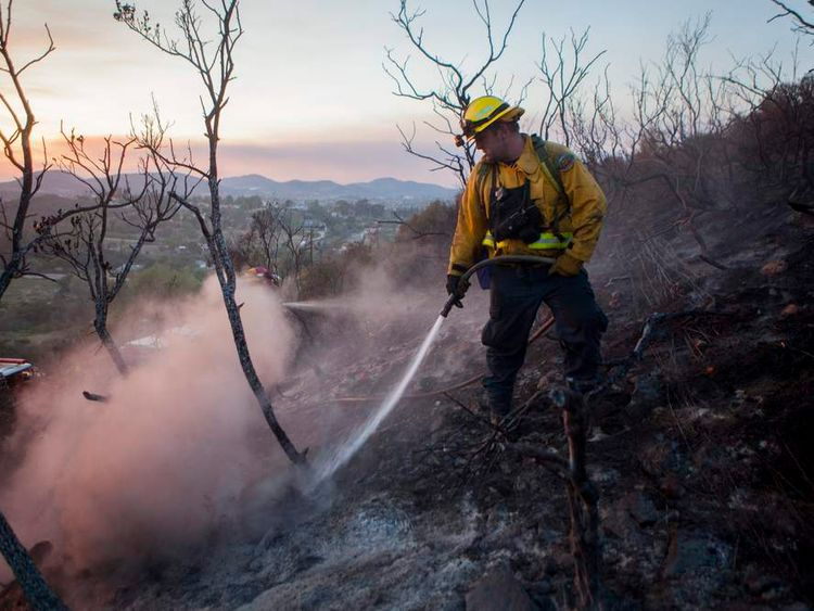 Fire crew put out smouldering embers from the Cocos Fire in San Marcos