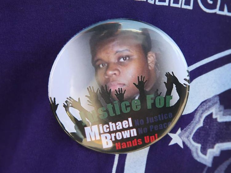 A resident wears a button featuring a picture of Michael Brown