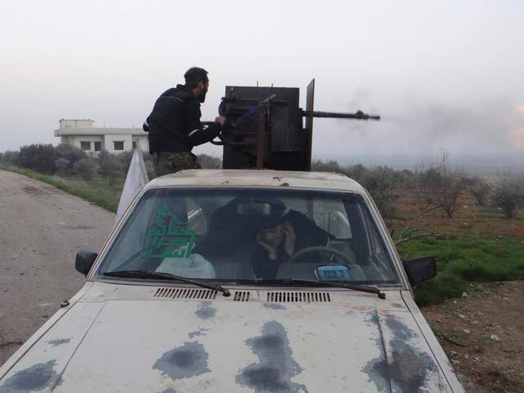 A Free Syrian Army fighter fires an anti-aircraft artillery weapon during an air strike in Taftanaz