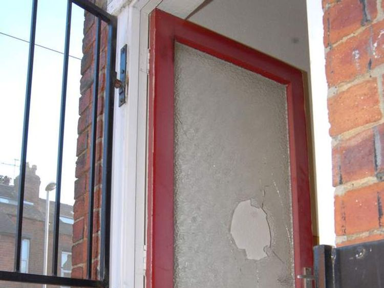 The damaged front door through which Leslie shot the police woman