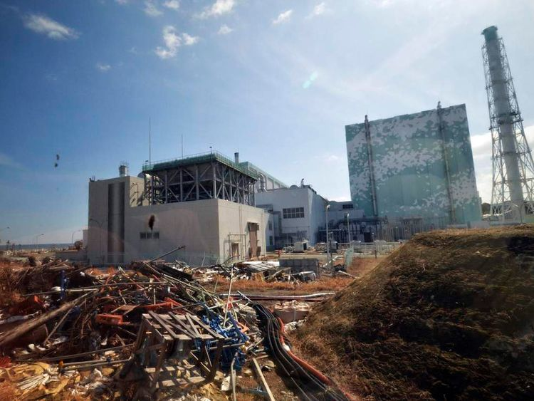 Debris is seen in front of the crippled TEPCO's Fukushima Daiichi nuclear power plant No. 6 reactor building in Fukushima prefecture