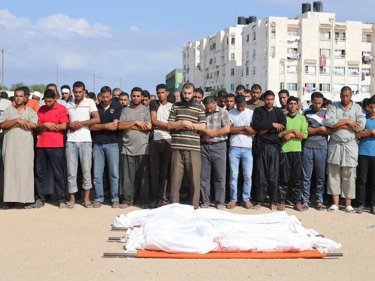 Palestinians pray over the dead bodies of three family members