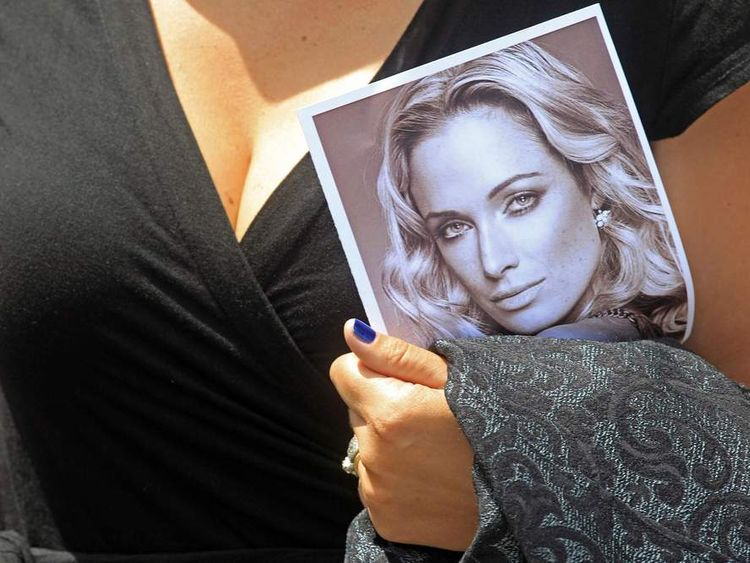 A woman holds a photo of Reeva Steenkamp, as she leaves her funeral