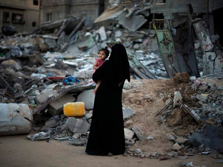 A Palestinian woman holds her daughter as they stand in front of their house, which witnesses said were destroyed in an Israeli offensive, during a 72-hour truce in Beit Hanoun town in the northern Gaza Strip