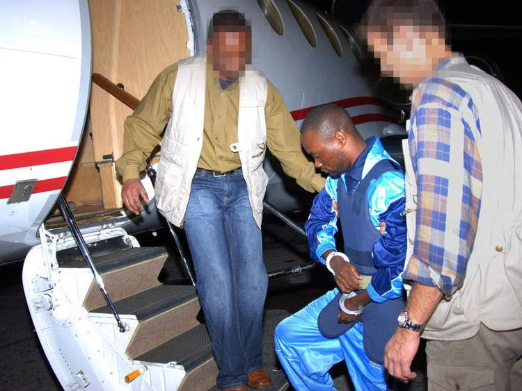 Democratic Republic of Congo militia chief Germain Katanga (C), 29, boards a plane at Kinshasa airport to be extradited to The Hague in The Netherlands, 18 October 2007