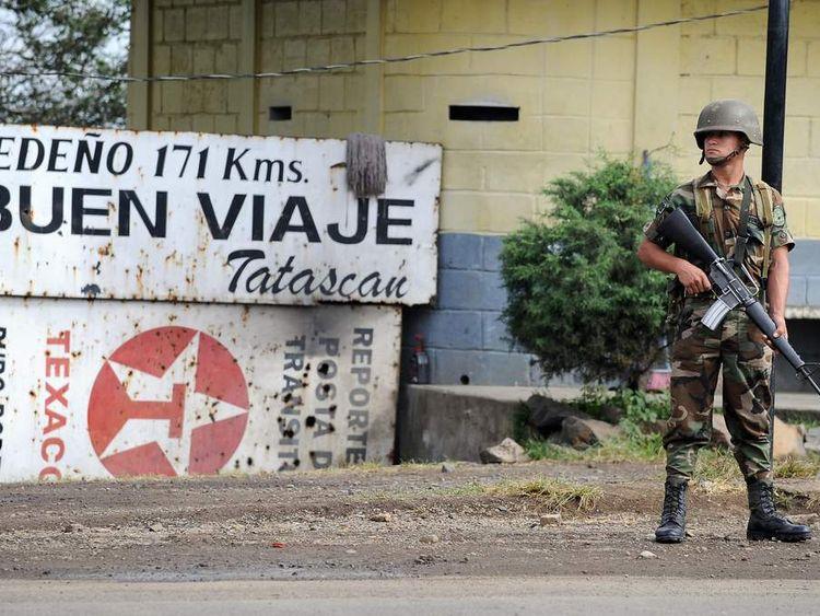 A Honduran soldier keeps watch at a checkpoint near the border
