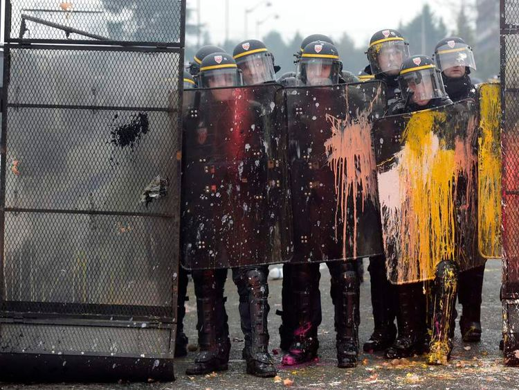 French CRS riot police are covered with paint during clashes with demonstrators in front of tyre maker Goodyear Dunlop France headquarters in Rueil Malmaison