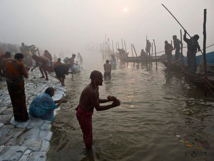 """Hindu devotees take a holy dip in the waters of river Ganges amid fog ahead of the """"Kumbh Mela"""" in Allahabad"""