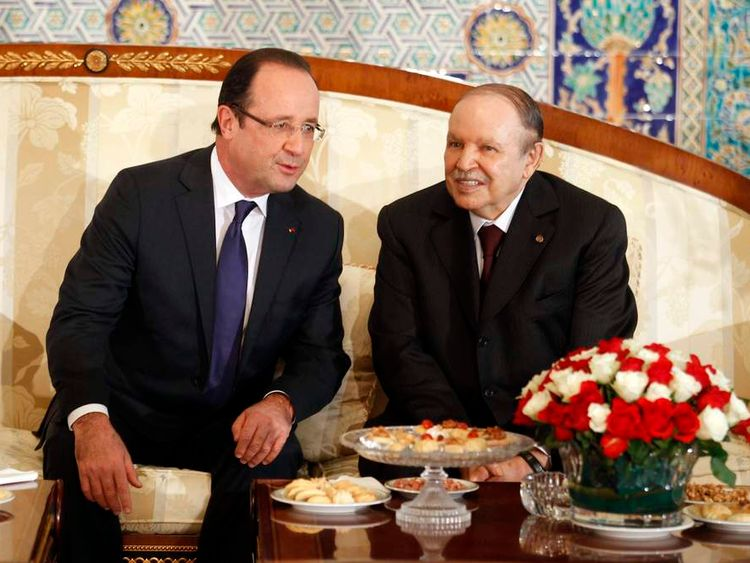 France's President Francois Hollande talks to Algerian President Abdelaziz Bouteflika at Algiers airport