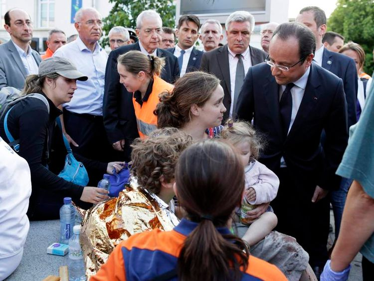 Francois Hollande comforts victims during a visit on the site of an intercity train accident at the Bretigny-sur-Orge train station near Paris