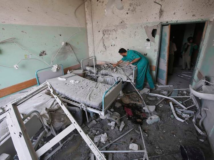 Palestinian medic inspects a shell-damaged hospital in Gaza