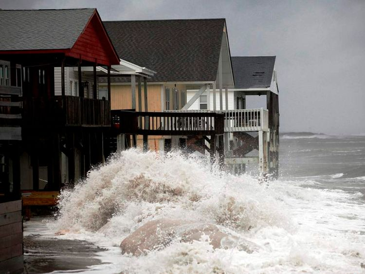 A wave crashes over the protecting sandbags in front of the houses on the east side of Ocean Isle Beach during Hurricane Sandy in Ocean Isle Beach, North Carolina, October 27, 2012.