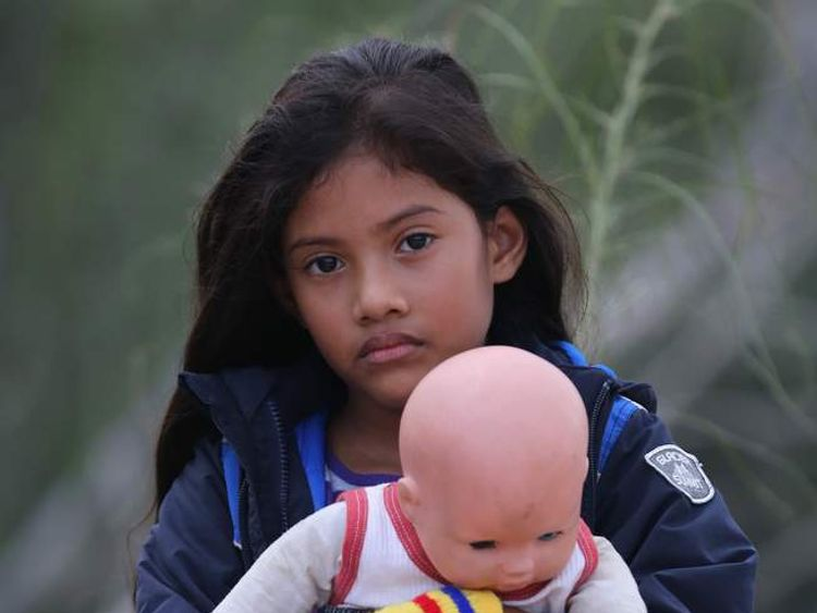 Salvadorian Stefany Marjorie, 8, holds her doll after crossing the Rio Grande