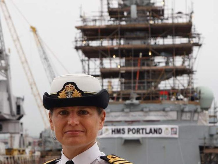 Commander Sarah West in front of HMS Portland