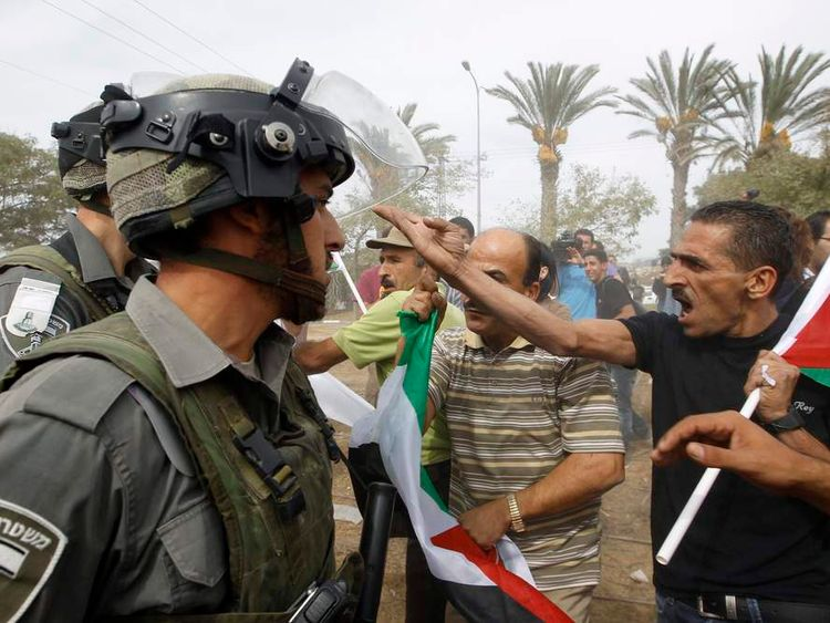 Israeli border police officers stand in front of Palestinian activists trying to block a road in Modiin Illit