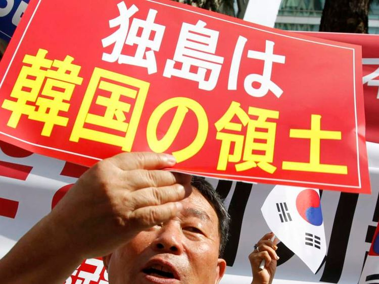 Members of the Korea Freedom Federation shout slogans during an anti-Japan protest in front of the Japanese embassy in Seoul