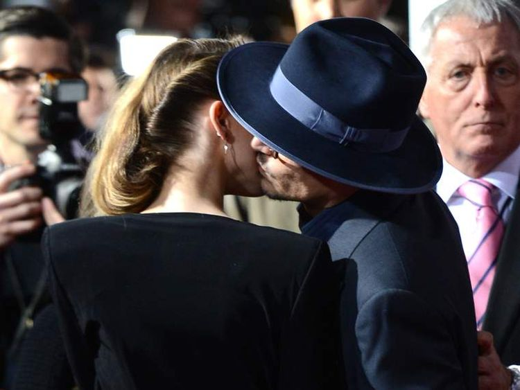 """Actor Johnny Depp and actress Amber Heard kiss at the premiere of """"3 Days to Kill"""" in LA"""