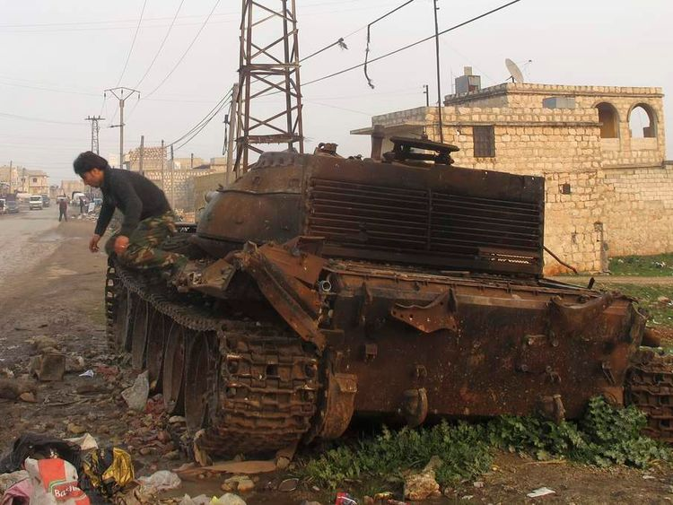 A member of the Free Syrian Army jumps from a destroyed military tank that belonged to forces loyal to president Bashar al Assad, in the Khan al-Assal area near Aleppo