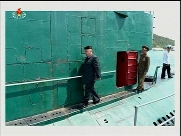 Kim Jong-un walks past what appears to be repair to outside of submarine