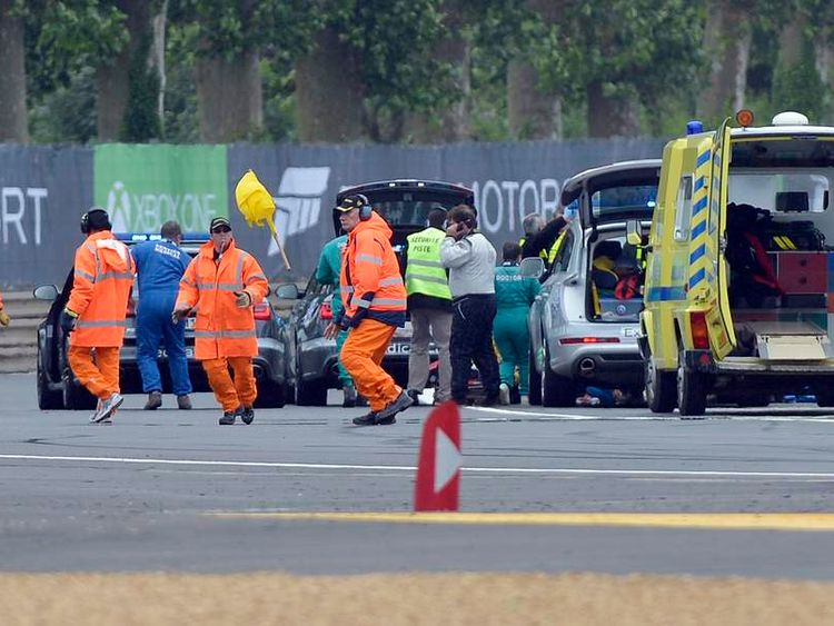 Security members work near the car of Denmark's Allan Simonsen during the Le Mans 24-hour sportscar race in Le Mans