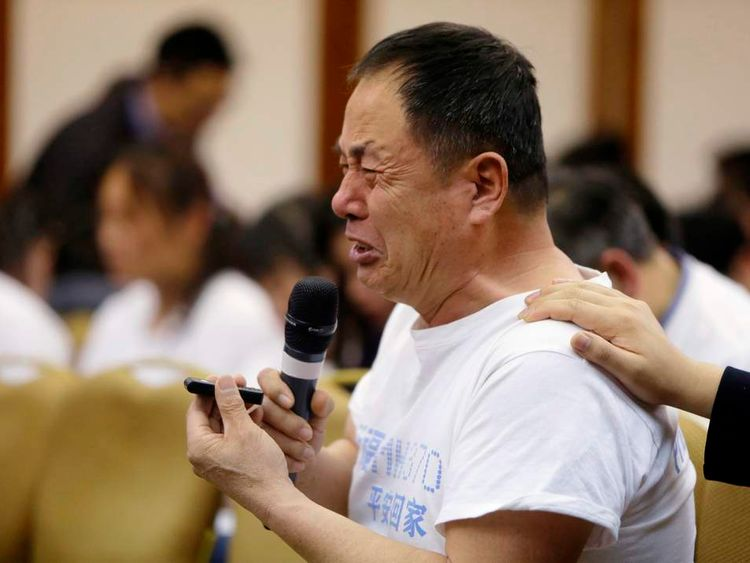 A father whose son was aboard Malaysia Airlines flight MH370, cries as he asks a question during a briefing