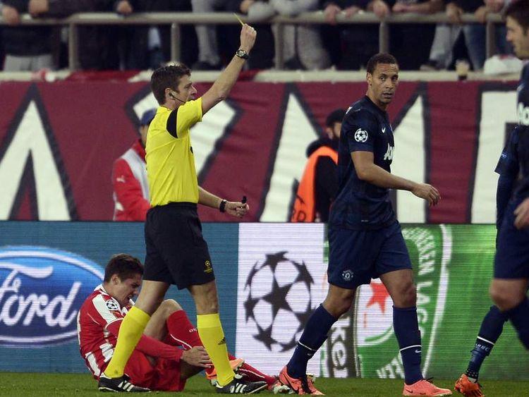 Rio Ferdinand receives a yellow card