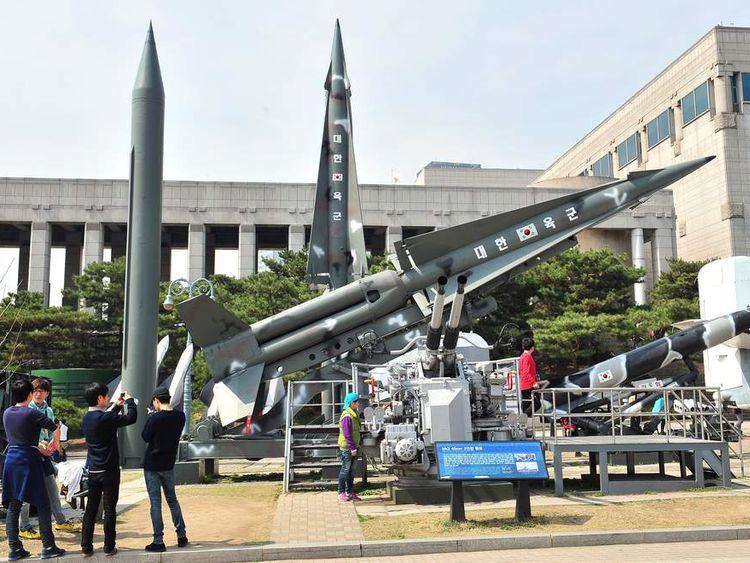 Visitors look at replicas of North Korean Scud-B missile (L) and South Korean Nike missiles at the Korean War Memorial