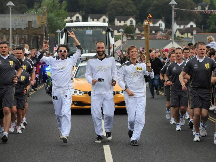 Muse - Matt Bellamy, Dominic Howard and Christopher Wolstenholme carry the Olympic flame between Torquay and Teignmouth
