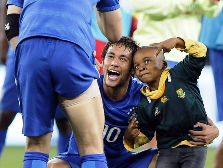 A South African boy who invaded the pitch jokes with Brazil's forward Neymar at the end of a friendly football match between South Africa and Brazil at Soccer City stadium in Soweto